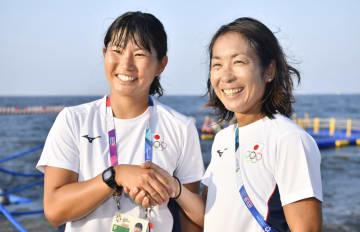 女子470級のレースを終え、笑顔で握手する吉田(右)、吉岡組。金メダルを獲得した=ジャカルタ(共同)