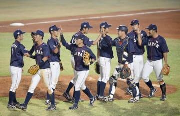台湾に勝利し、タッチを交わす日本ナイン=ジャカルタ(共同)