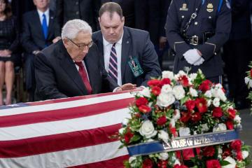 マケイン上院議員のひつぎに手を添えるキッシンジャー元米国務長官=8月31日、ワシントン(UPI=共同)