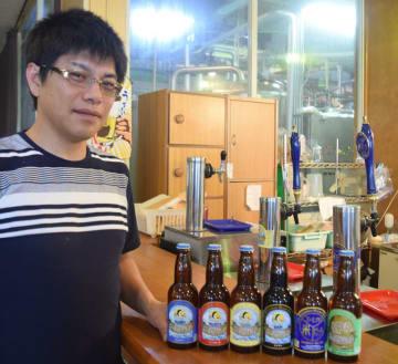 ずらりと並べた地ビールに「自信があります」と胸を張る「寒菊銘醸」の佐瀬社長。ガラスの奥には地ビール工場が広がる=山武市松尾町