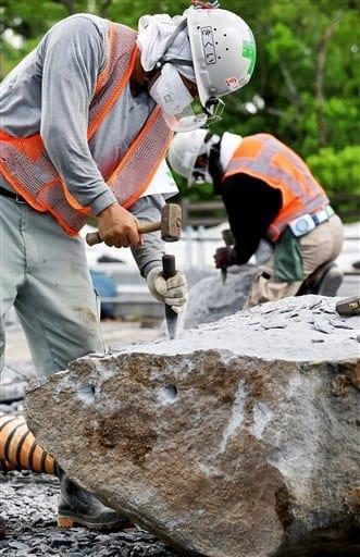 熊本城大天守の石垣に使う新しい石を手作業で加工する石工=31日、熊本市(小野宏明)