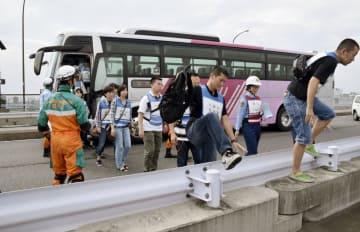 東京都と神奈川県境の国道246号で行われた訓練で、バスが衝突事故を起こしたと想定し乗客を誘導する警視庁の警察官(左端)ら=1日午前