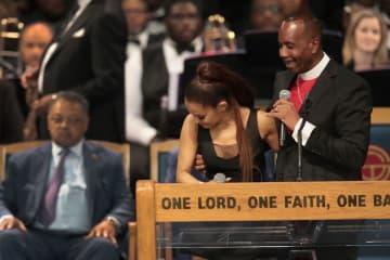 米デトロイトの教会で歌い終わった歌手アリアナ・グランデさん(左)と話す牧師=8月31日(ゲッティ=共同)