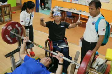 トレーニング器具を確かめるラオス代表のピア選手(手前)ら=別府市の太陽の家「サンスポーツセンター」
