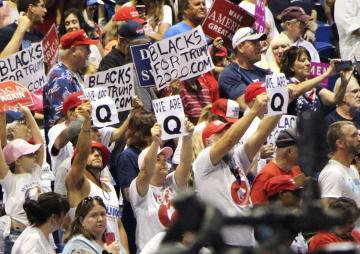 トランプ米大統領の集会で「私たちはQ」と書いた紙を掲げるトランプ氏の支持者ら=7月、米フロリダ州タンパ(共同)