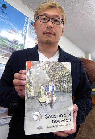 ジャパンエキスポで「ACBDアジア賞」を受賞した漫画「Sous un ciel nouveau」を持つ藤井さん(守山市吉身4丁目・まちおこし)