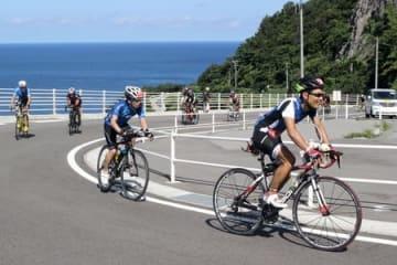 「Z坂」の愛称で知られる急坂をバイクで駆け上がる出場者=2日、佐渡市岩谷口