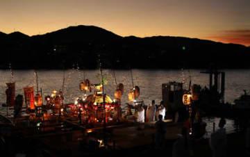 夕空を背に黒津浜の御旅所で神事が営まれる。辺りが暗くなると、神輿を彩る電飾の光が鮮やかに浮かぶ(17日午後7時5分、大津市黒津4丁目・瀬田川左岸)
