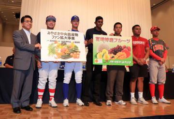 戸敷市長(左)から本県産の野菜や果物の目録パネルを受け取った各国・地域の選手たち=2日午後、宮崎市・宮崎観光ホテル