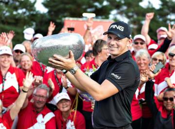 欧州ゴルフのメード・イン・デンマーク、プレーオフを制し、トロフィーを掲げるマット・ウォレス=2日、オーフス(ロイター=共同)
