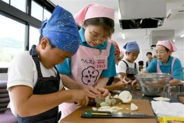 食生活改善推進委員のアドバイスを受けながらカレー作りに挑戦する子どもたち=玉名市