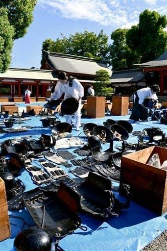 秋晴れの空の下、神幸行列の随兵が身に着ける甲冑などを虫干しする神職ら=熊本市中央区