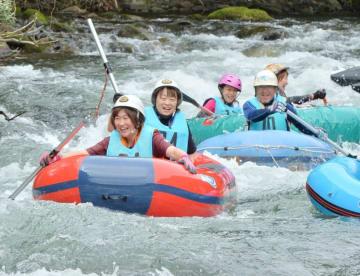 急流に差し掛かりバランスを取りながら川を下る参加者