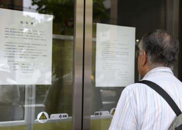 ケフィア事業振興会の本社前で破産を知らせる張り紙を見る男性=3日午前、東京都千代田区