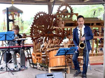 水車音楽装置「ミル」とともに軽快な音色を奏でる岡淳さん(右)
