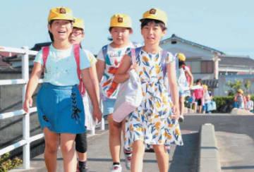 日焼けした顔で元気に登校する高田小学校の児童=3日午前、豊後高田市新地