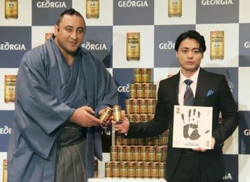 缶コーヒーの新製品発表会に出席したジョージア出身の栃ノ心。右は俳優の山田孝之さん=3日、東京都新宿区