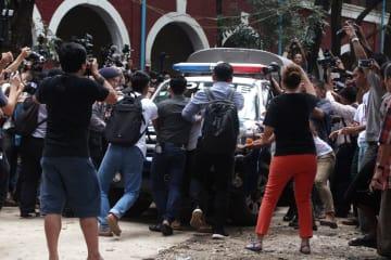 ミャンマーのヤンゴンで、有罪判決を受けたロイター通信の記者2人を乗せた警察車両の前に立つ地元記者ら=3日(ロイター=共同)