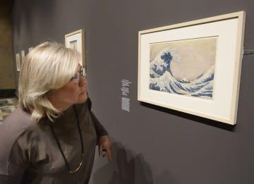3日、モスクワのプーシキン美術館に展示された、葛飾北斎の「富嶽三十六景 神奈川沖浪裏」に見入るロシア人女性(共同)