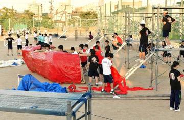 台風に備え、体育祭の作り物をグラウンドから移動し足場を解体する生徒ら=9月3日午後5時45分ごろ、福井県福井市の藤島高校