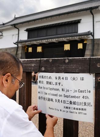 台風21号の接近に備え閉城の案内を取り付ける関係者(3日午後4時42分、京都市中京区・二条城)