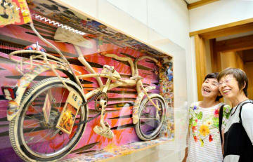 自転車などを組み込んだダイナミックな作品が並ぶ智内さんの絵本原画展