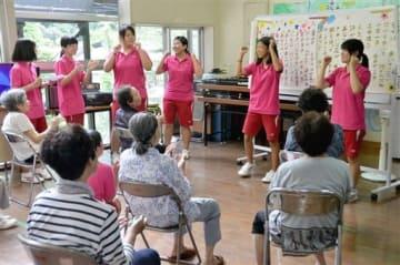 地元住民に介護予防体操を指導する多良木高の生徒たち=多良木町