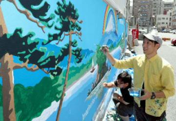 ビルの壁面に富士山や松島の風景を描く宮崎勇次郎さん(右)=大分市府内町の金剛ビル