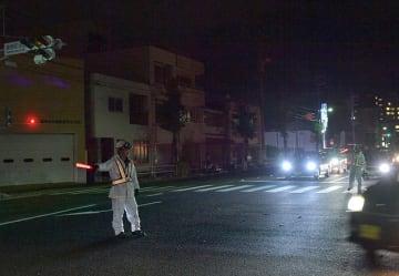 台風21号の影響で信号機が停電になり手信号で車を誘導する警察官=4日午後7時30分、岐阜市本荘