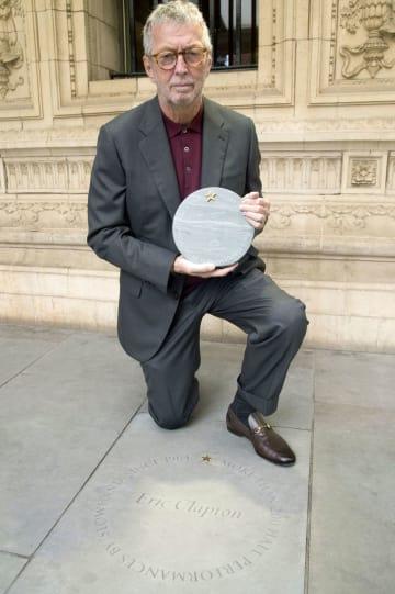 4日、ロンドンのロイヤル・アルバート・ホールで、歩道に刻まれた名前(下)を前にポーズをとるエリック・クラプトンさん(同ホール提供・共同)