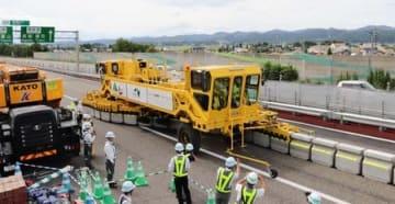 専用車両を使ってコンクリ-ト製の防護柵を移動させ、車線を規制する作業=4日、長岡市王番田町の北陸道