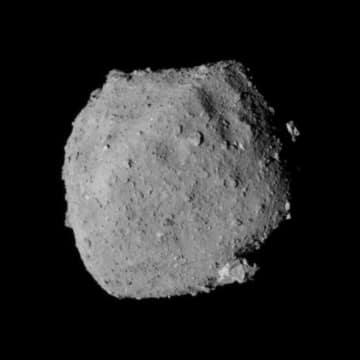 上空22キロから撮影した小惑星りゅうぐう。左上が北極側、右下が南極側(JAXA、東大など提供)