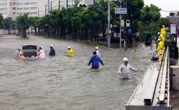 冠水した交差点で車が立ち往生。警察官らが運転手を救出した=4日午後2時16分、神戸市中央区東川崎町1