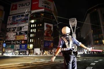 停電で信号が消えた北海道札幌市中心部のすすきの交差点で、交通整理に当たる警察官=9月6日午前3時48分