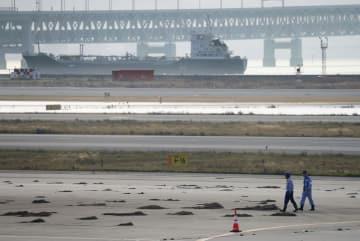 土砂などが残る関西空港。奥は連絡橋に衝突したタンカー=6日午前6時38分