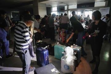 停電した旭川空港のターミナルで、懐中電灯の明かりを頼りに手荷物を確認する人たち=6日午後