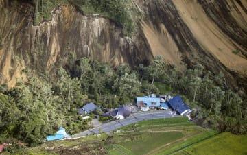 地震による土砂崩れで倒壊した家屋=6日午前8時13分、北海道厚真町(共同通信社機から)