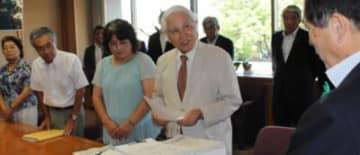 署名簿を提出する松本文六・原告団共同代表(左から4人目)