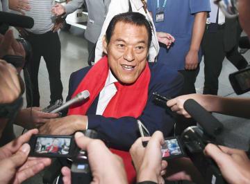6日、北京国際空港で記者団の取材に応じるアントニオ猪木参院議員(共同)