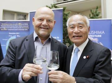 東北の日本酒を振る舞い、東日本大震災からの復興をアピールする行事に参加する吉野復興相(右)=6日、ヘルシンキ(共同)