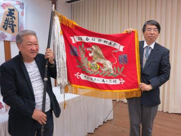 大山康晴氏寄贈の優勝旗を授与する山田大使(右)と高嶋さん(左)