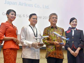 包括的な業務提携契約を結び、ガルーダ・インドネシア航空のパハラ・ヌグラハ・マンスリCEO(中央左)と記念写真に納まる日航の藤田直志副社長(同右)=6日、ジャカルタ近郊(共同)