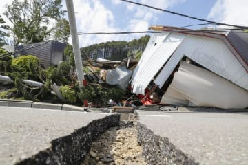 地震で大きく亀裂の入った道路と倒れた建物=6日午後1時6分、北海道厚真町吉野地区