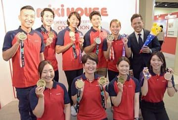 アジア大会に出場した選手たちと野村ゼネラルマネジャー(右上)=6日、八尾市のミキハウス本社