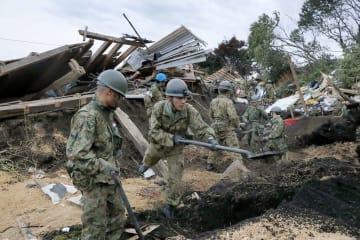 土砂崩れで倒壊した建物周辺を捜索する自衛隊員=7日午前5時18分、北海道厚真町吉野地区