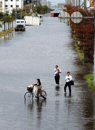 冠水した道路を歩く人=4日午後5時32分、神戸市東灘区の六甲アイランド(撮影・大森 武)