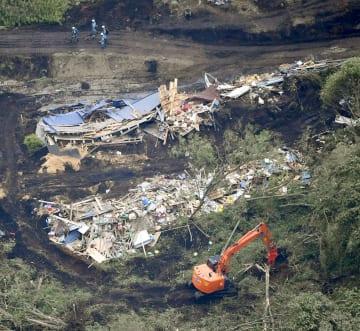 土砂崩れで倒壊した建物周辺を捜索する警察官ら=7日午前8時26分、北海道厚真町(共同通信社ヘリから)