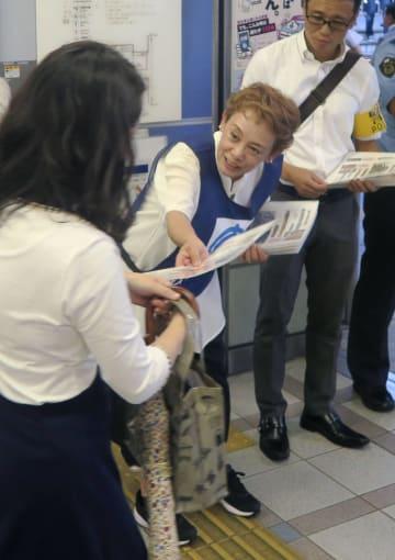 事件から14年を迎えるのを前に、情報を求めるビラを配る天海としさん(中央)=7日午後、愛知県豊明市の名古屋鉄道前後駅