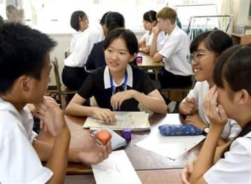 英語の授業で中国の高校生(中央)を囲んで意見交換する熊本北高の生徒=熊本市北区