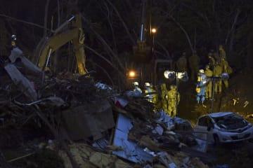 地震による土砂崩れなどで倒壊した家屋の周辺で、暗くなっても安否不明者の捜索を続ける自衛隊員ら=7日午後5時57分、北海道厚真町吉野地区